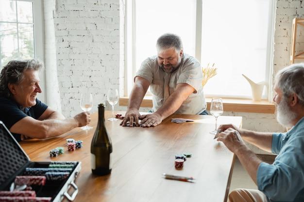 Gruppe von glücklichen reifen freunden, die karten spielen und wein trinken
