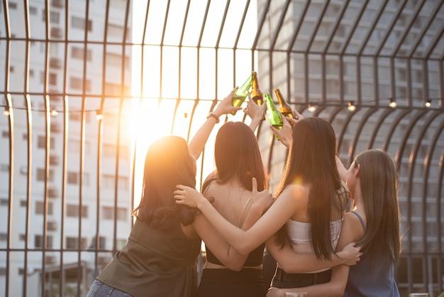 Gruppe von glücklichen schönen jungen asiatischen freundinnen auf der rückseite oder rückseite angehoben hand halten flasche bier tanz und toast zusammen auf außenterrasse terrasse am abend des outdoor-clubs.