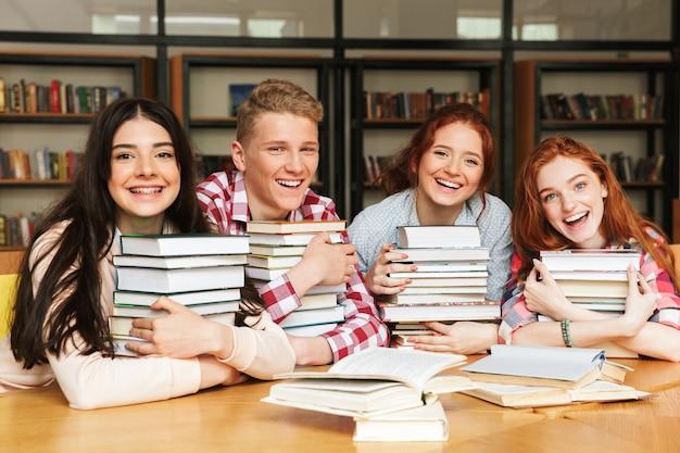 Gruppe von glücklichen teenagern, die an der bibliothek sitzen