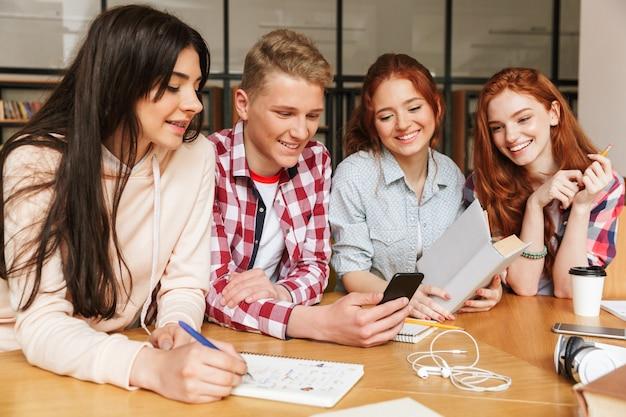 Gruppe von glücklichen teenagern, die hausaufgaben machen