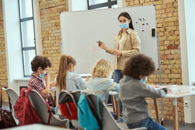 Gruppe von grundschulkindern und lehrerinnen, die während des coronavirus eine schutzmaske tragen