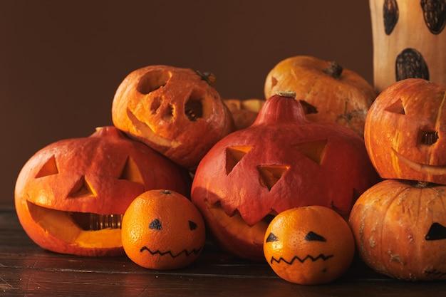 Gruppe von gruseligen kürbissen, kürbissen und mandarinen geschnitzt und gemalt für halloween-partydekoration gegen braune wandoberfläche, studioaufnahme