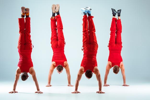 Gruppe von gymnastischen akrobatischen kaukasischen männern auf gleichgewichtspose