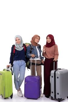 Gruppe von hijab-reisenden, die koffer und stehende tragetasche halten