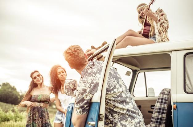 Gruppe von hippie-artfreunden, die zusammen mit einem vintagen van reisen