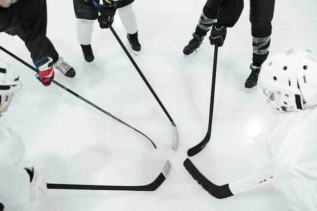 Gruppe von hockeyspielern in sportuniform, handschuhen und schlittschuhen, die im kreis auf der eisbahn stehen und ihre stöcke vor sich halten