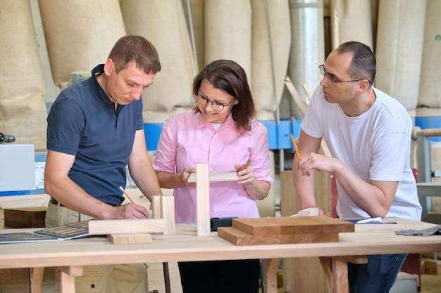 Gruppe von industriellen kunden, designern oder ingenieuren und arbeitern, die gemeinsam an einem projekt von holzmöbeln arbeiten. teamwork in der schreinerei