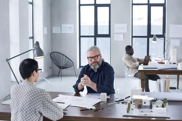 Gruppe von ingenieuren, die bei besprechungen am tisch sitzen und in einem modernen büro mit blaupausen arbeiten