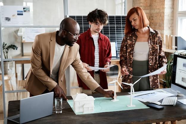 Gruppe von ingenieuren, die ein neues projekt mit modellen entwickeln, während sie im büro am tisch stehen