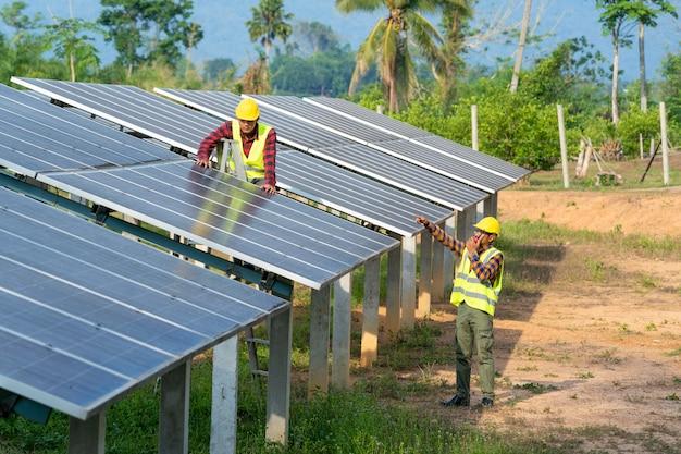 Gruppe von ingenieuren, die solarmodule im routinebetrieb eines solarkraftwerks prüfen, betrieb und wartung in solarkraftwerken, solarkraftwerken zur innovation von grüner energie fürs leben.