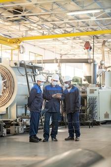 Gruppe von ingenieuren in schutzhelmen, die in der industriewerkstatt stehen und über technische zeichnungen auf dem tablet diskutieren