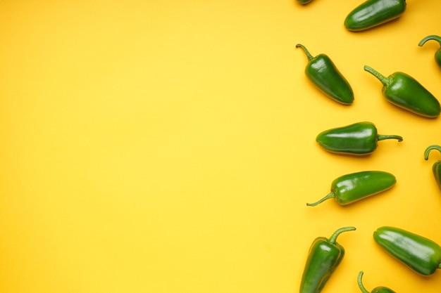 Gruppe von jalapenopfeffer auf gelbem hintergrund, platz für text, ansicht von oben. grüne chilischote.