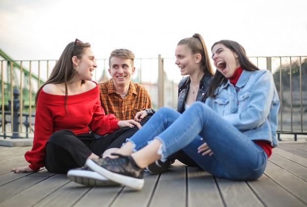 Gruppe von jugendlichen sitzen auf einer terrasse
