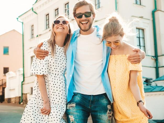 Gruppe von jungen drei stilvollen freunden, die in der straße aufwerfen. modemann und zwei süße mädchen gekleidet in lässige sommerkleidung. lächelnde models, die spaß an sonnenbrillen haben. fröhliche frauen und männer bei susnet