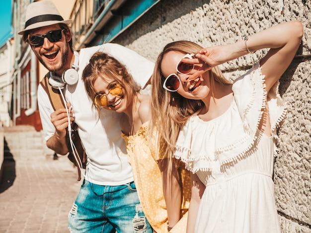 Gruppe von jungen drei stilvollen freunden, die in der straße aufwerfen. modemann und zwei süße mädchen gekleidet in lässige sommerkleidung. lächelnde models, die spaß an sonnenbrillen haben. fröhliche frauen und männer im freien