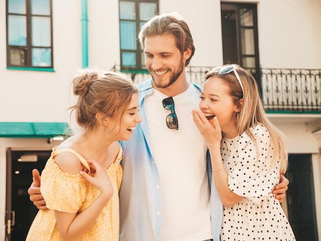 Gruppe von jungen drei stilvollen freunden, die in der straße aufwerfen. modemann und zwei süße mädchen gekleidet in lässige sommerkleidung. lächelnde models, die spaß an sonnenbrillen haben. fröhliche frauen und männer unterhalten sich