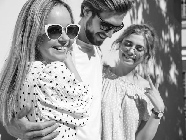 Gruppe von jungen drei stilvollen freunden, die in der straße aufwerfen. modemann und zwei süße mädchen gekleidet in lässige sommerkleidung. lächelnde models, die spaß an sonnenbrillen haben. vorsichtige frauen und kerle, die verrückt werden