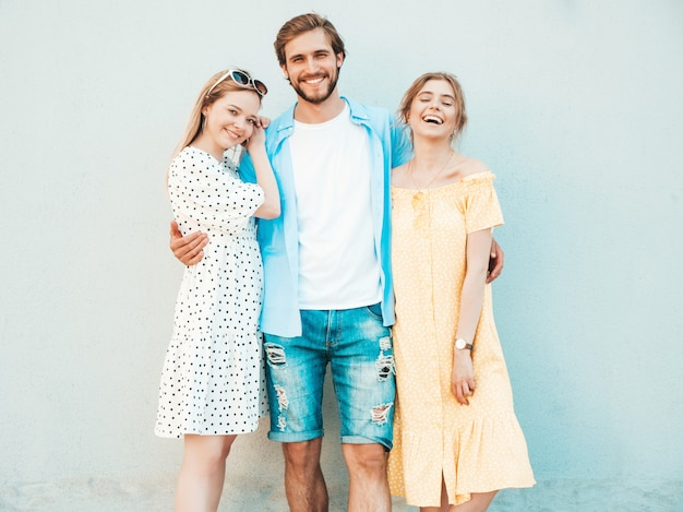 Gruppe von jungen drei stilvollen freunden, die in der straße aufwerfen. modemann und zwei süße mädchen gekleidet in lässige sommerkleidung. lächelnde models, die spaß in der nähe der wand haben. vorsichtige frauen und männer im freien