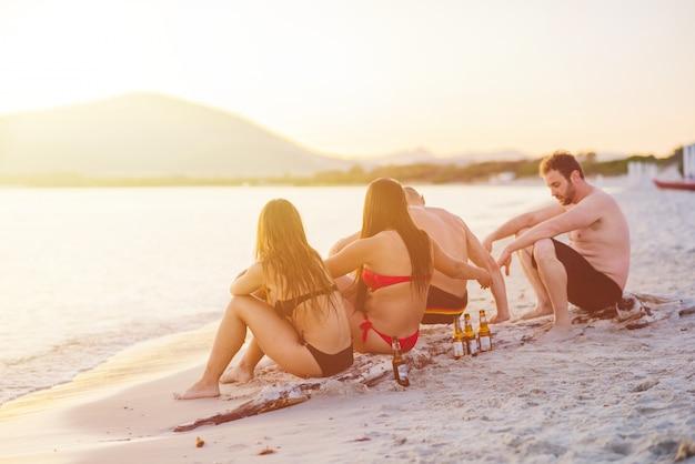 Gruppe von jungen freunden, die strand sitzen und vorbei schauen