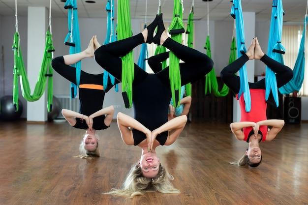 Gruppe von jungen leuten, die yoga auf hängematte im gesundheitsclub praktizieren. fitness, dehnung, gleichgewicht, bewegung und gesunde lebensweise menschen