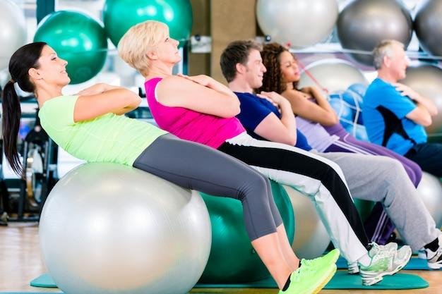 Gruppe von jungen und älteren leuten, die im fitnessstudio trainieren