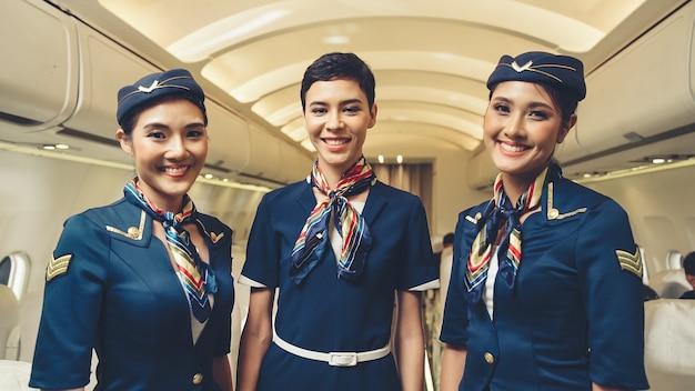 Gruppe von kabinenpersonal oder stewardess im flugzeug