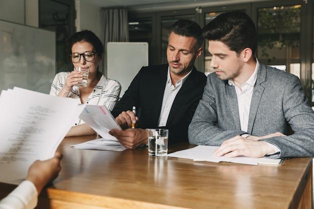 Gruppe von kaukasischen arbeitgebern in formeller kleidung, die am tisch im büro sitzen und junge frau während des vorstellungsgesprächs konsultieren - geschäfts-, karriere- und rekrutierungskonzept
