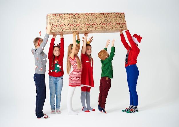 Gruppe von kindern, die das halten der großen geschenkbox vorbereiten