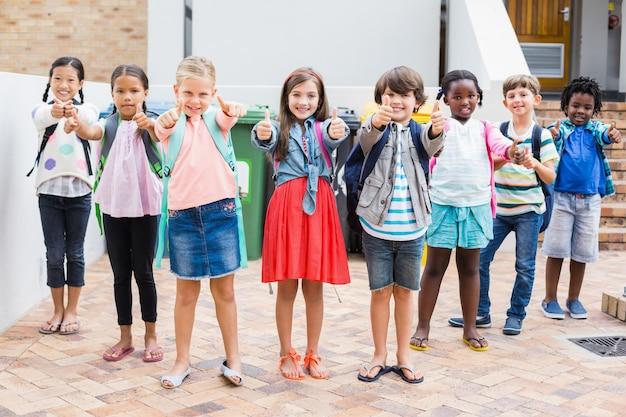 Gruppe von kindern, die daumen oben auf schulterrasse zeigen