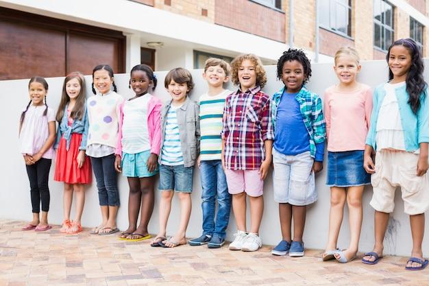 Gruppe von kindern, die in einer reihe auf schulterrasse stehen