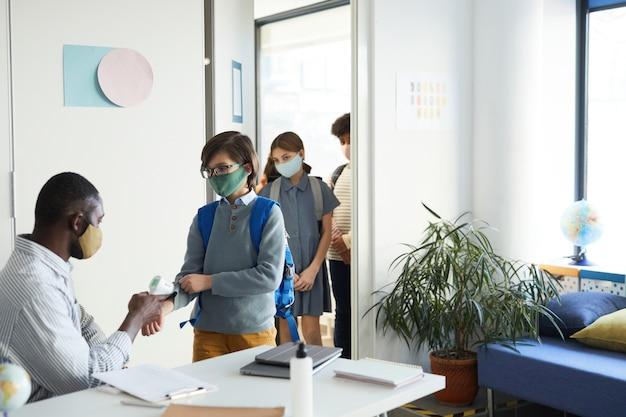 Gruppe von kindern, die masken tragen, die das klassenzimmer in der schule betreten, wobei der lehrer die temperatur mit infrarot-thermometer überprüft, covid-sicherheit