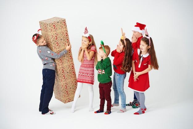 Gruppe von kindern, die weihnachtsüberraschung vorbereiten