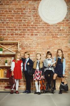 Gruppe von kindern, die zeit nach der schule zusammen verbringen. hübsche freunde, die sich nach dem unterricht ausruhen, bevor sie anfangen, hausaufgaben zu machen. modernes loft-interieur. schulzeit, freundschaft, bildung, zusammengehörigkeitskonzept.
