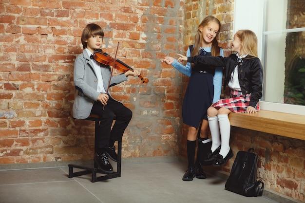 Gruppe von kindern, die zeit nach der schule zusammen verbringen. hübsche freunde, die sich nach dem unterricht ausruhen, bevor sie anfangen, hausaufgaben zu machen