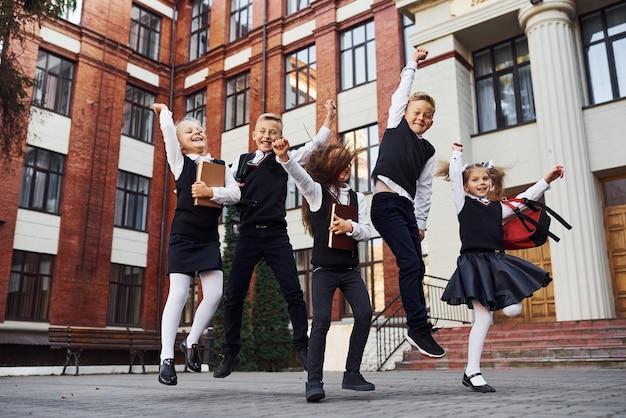Gruppe von kindern in schuluniform, die zusammen in der nähe des bildungsgebäudes springen und spaß im freien haben.