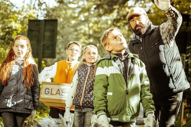 Gruppe von kindern und lehrern, die an einem guten tag müll sammeln und im wald sortieren