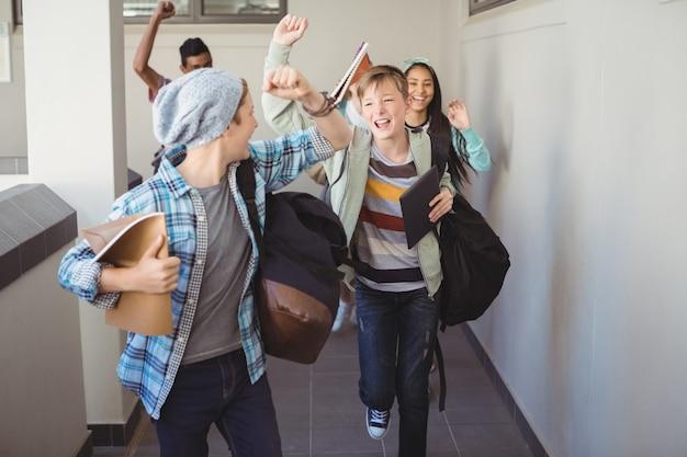 Gruppe von klassenkameraden, die im korridor laufen