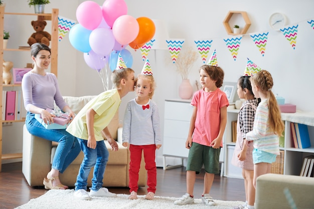 Gruppe von kleinen freundlichen kindern, die flüsterspiel im wohnzimmer spielen, während junge frau mit geschenken im sessel in der nähe sitzen