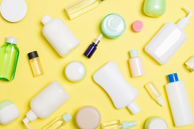 Gruppe von körperpflegeflaschen aus kunststoff flache zusammensetzung mit kosmetischen produkten auf gelbem hintergrund leeren raum für sie entwerfen. satz weiße kosmetische behälter, draufsicht mit kopienraum.