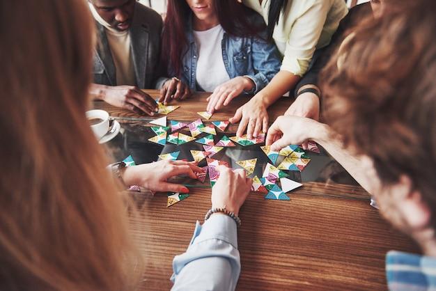 Gruppe von kreativen multietnischen freunden, die am holztisch sitzen. leute, die spaß beim brettspiel haben
