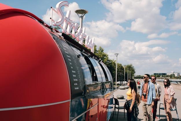 Gruppe von kunden, die das menü durchsehen, während sie am street food truck stehen