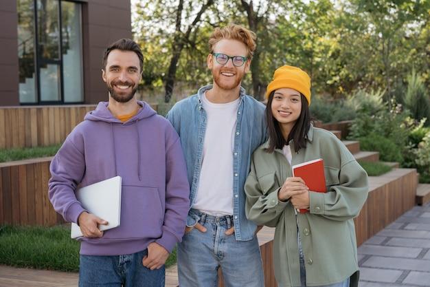 Gruppe von lächelnden gemischtrassigen universitätsstudenten, die zusammen stehen