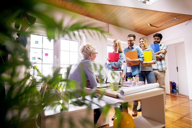 Gruppe von lächelnden und nervösen jungen leuten, die in einer reihe mit einem ordner in der hand vor einem interview mit dem unternehmer im büro stehen