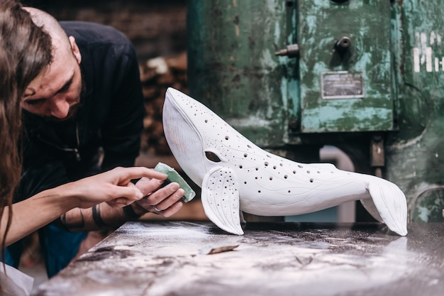 Gruppe von leuten, die lieblingsjob in der werkstatt genießen. die leute arbeiten sorgfältig an keramikwalen