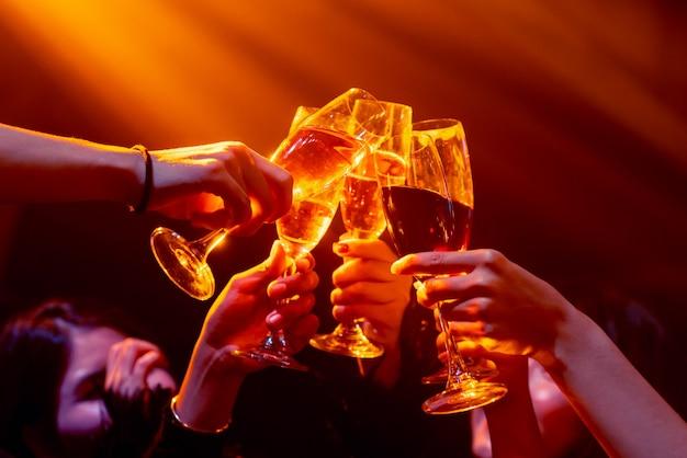 Gruppe von leuten röstet getränke auf der party im tanzclub