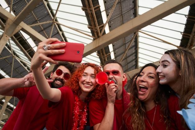 Gruppe von leuten verschiedener rassen, die ihr team aufmuntern und ein selfie im fußballstadion machen taking