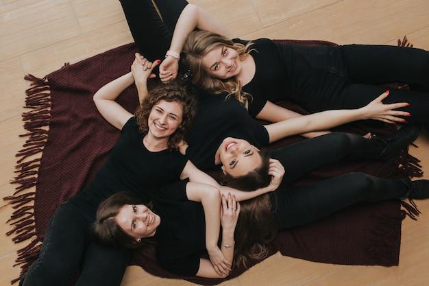 Gruppe von mädchen in der schwarzen kleidung, die auf dem boden auf einer braunen decke liegt