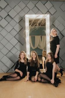 Gruppe von mädchen in schwarz posiert in der nähe des spiegels auf einer grauen wand