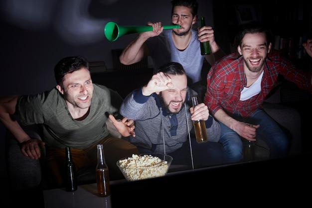 Gruppe von männern, die bier trinken und fußball im fernsehen schauen
