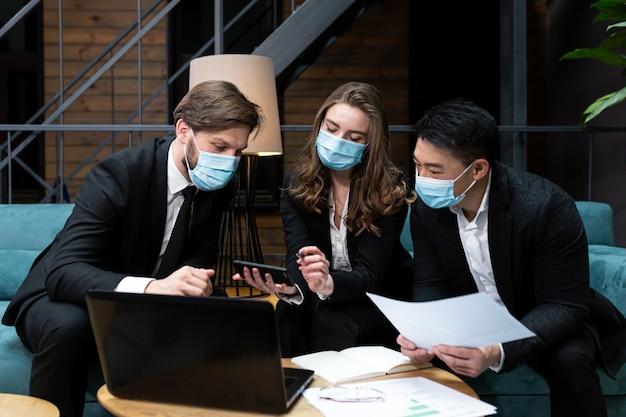 Gruppe von männern und frau halten geschäftstreffen nahe laptop, das schützende medizinische masken auf gesicht im konferenzraum trägt